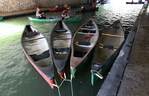Canoes are secured at the river bank at the 44th annual Ford Canoe Challenge along the River Walk on Saturday, August 4, 2012. About 100 teams that included Boy Scouts and Girls Scouts, corporate and celebrity participants took part in one of the oldest events held on the river. Photo: Kin Man Hui, SAN ANTONIO EXPRESS-NEWS / ©2012 San Antonio Express-News