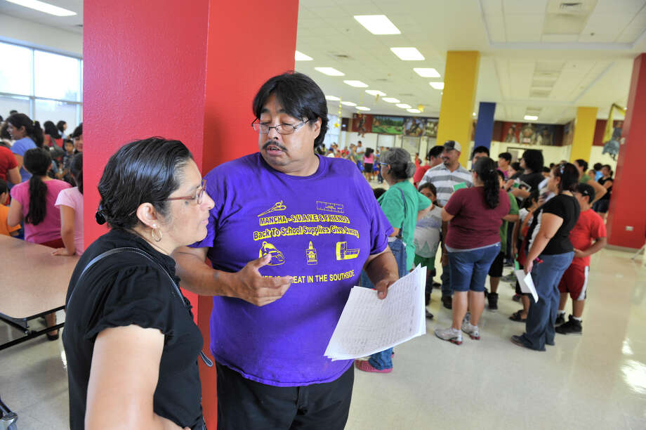 Juan Mancha talks with his wife, Diana, during the backpack and school supply giveaway at Harlandale in August. The businessman has worked tirelessly to help schoolchildren in the district. Photo: File Photo, San Antonio Express-News