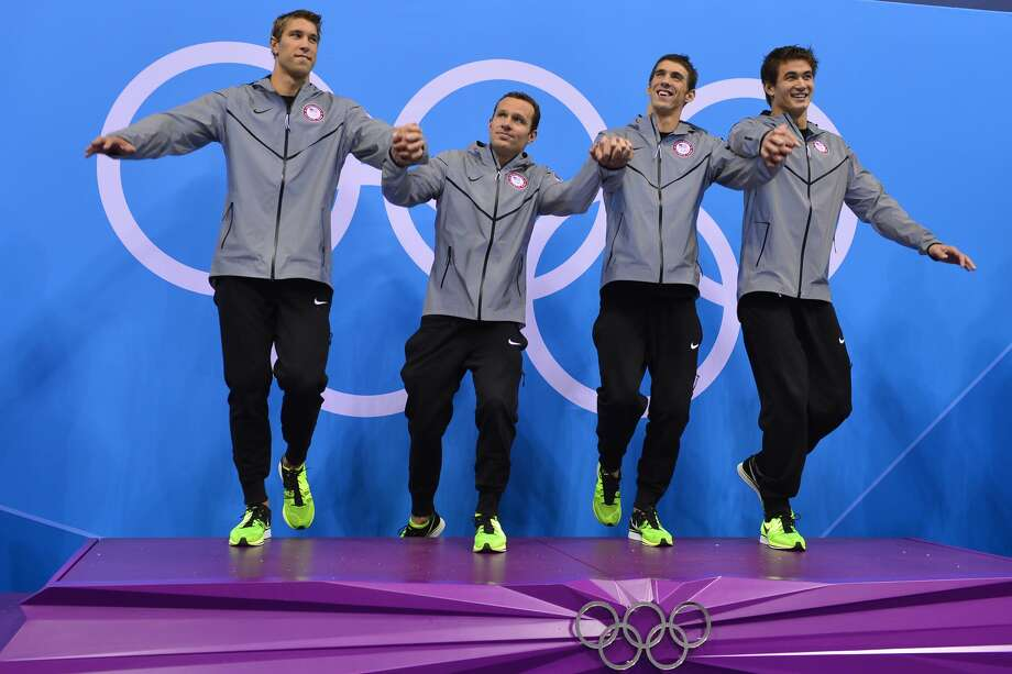 (L-R) US swimmers Matthews Grevers, Brendan Hansen, Michael Phelps and Adrian Nathan pose on the podium after winning gold in the men's 4x100 medley relay final during the swimming event at the London 2012 Olympic Games on August 4, 2012 in London. AFP PHOTO / FABRICE COFFRINIFABRICE COFFRINI/AFP/GettyImages (AFP/Getty Images)