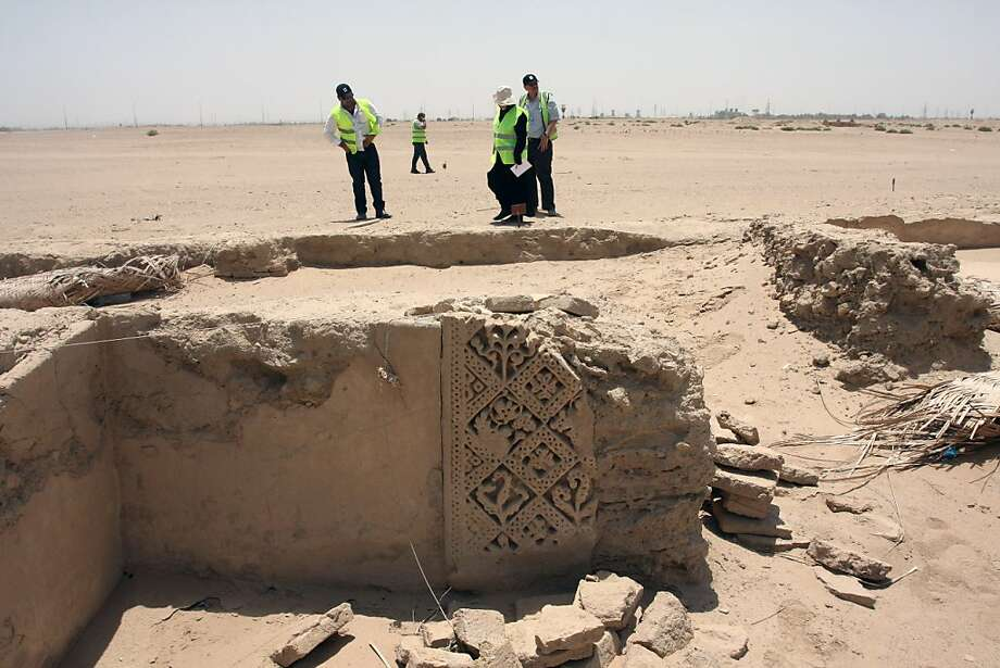 Archaeologists stand next to ruins that scholars think may be from the ancient city of Hira. Photo: Alaa Al-Marjani, Associated Press