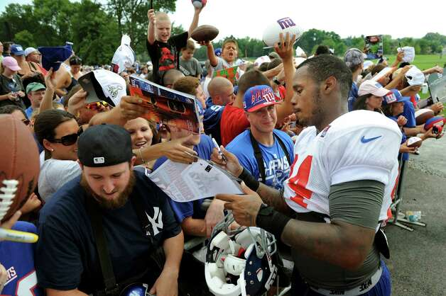 Christian Hopkins (84), right, of the New York Giants signs autographs for admiring fans at the end of Giants Camp on Saturday, Aug. 4, 2012, at UAlbany in Albany, N.Y. (Cindy Schultz / Times Union) Photo: Cindy Schultz / 00018641A