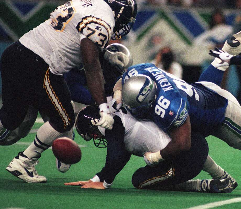 Sam Adams (98, on backside) and Cortez Kennedy (96) knock the ball loose as they  sack San Diego quarterback Sean Salisbury (8) in 1996. Isaac Davis (73) is on the play. Photo: GRANT M. HALLER