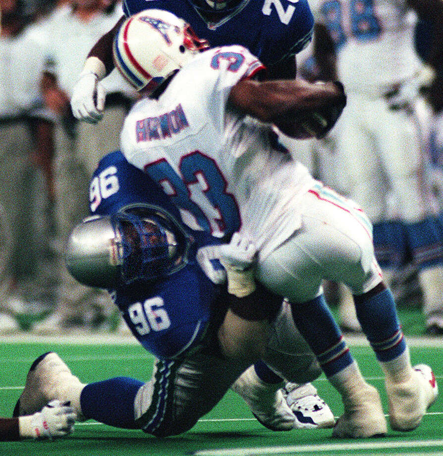 Cortez Kennedy (96) bends Houston's Ronnie Harmon (33) over backwards during a 1996 game in the Kingdome. Photo: GRANT M. HALLER