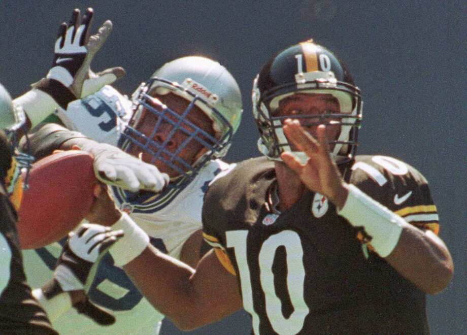 Seahawks defensive lineman Cortez Kennedy, left, knocks the ball out of the hand of Pittsburgh Steelers quarterback Kordell Stewart in the first quarter in Pittsburgh, Sept. 26, 1999. Photo: KEITH SRAKOCIC, Associated Press / AP
