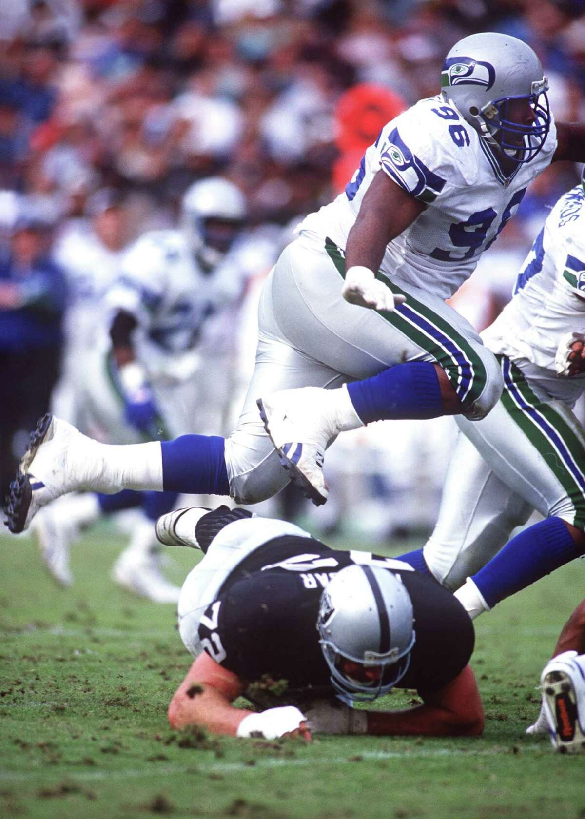 Seattle defensive tackle Cortez Kennedy hurdles Los Angeles offensive lineman Don Mosebar during the Seahawks' 27-23 loss to the Raiders at the Los Angeles Memorial Coliseum on Dec. 12, 1993.