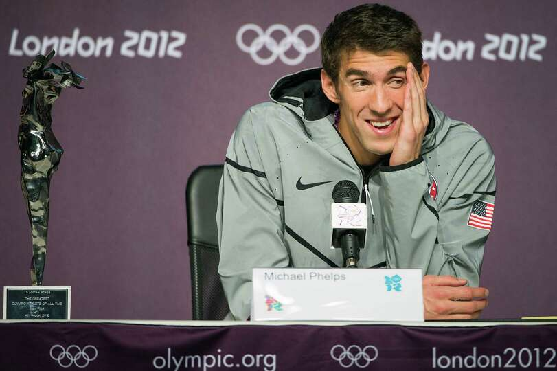 Swimmer Michael Phelps takes a question regarding his retirement as he sits next to a trophy during