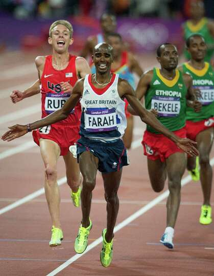 Mo Farah of Great Britain crosses the finish line ahead of Galen Rupp of the USA to win the men's 10