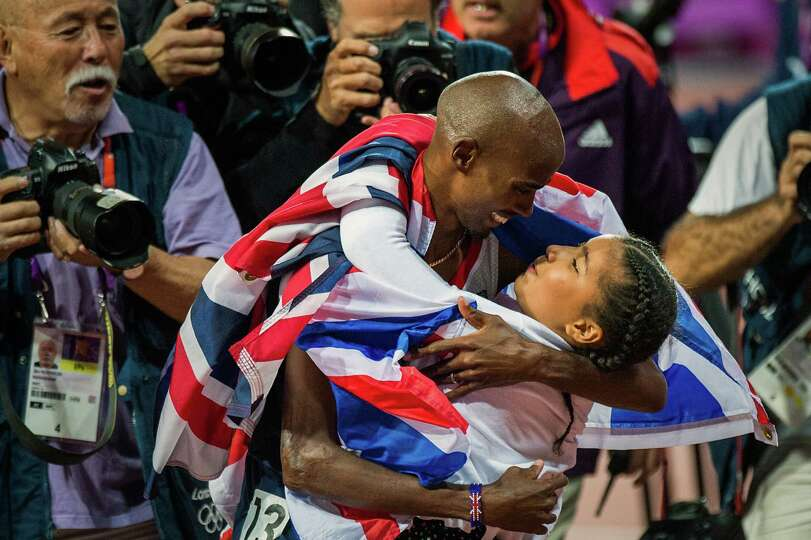 Mo Farah of Great Britain hugs his daughter Rihanna after winning the men's 10,000-meter final at th