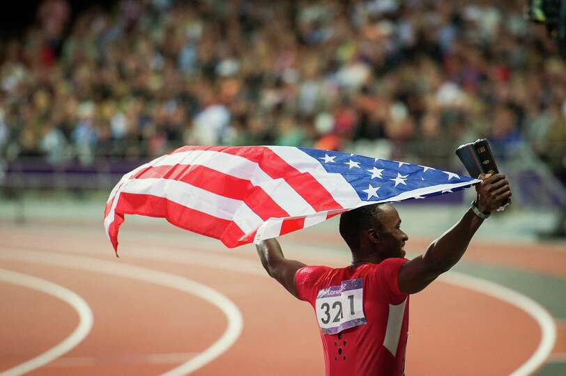 Will Claye of the USA carries an American flag and the Bible as he takes a victory lap to celebrate