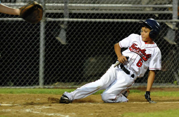 Connecticut's #6 Michael Ghiorzi slides safely into home plate, during 2012 Little League Baseball Eastern Regional action against Vermont in Bristol, Conn. on Saturday August 4, 2012. Photo: Christian Abraham / Connecticut Post