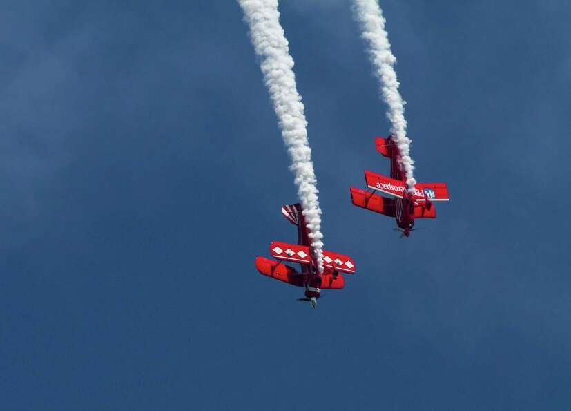 Two stunt pilots dive during a performance by Red Eagle Air Sports.