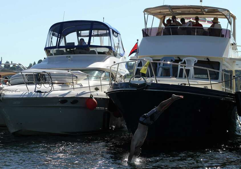 A man jumps off a boat into Lake Washington.