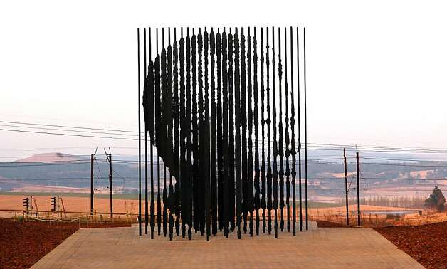 A sculpture of former South African President Nelson Mandela, is presented on August 4, 2012 in Howick, 90 kms South of Durban, commemorating the 50th anniversary of Mandela's capture by the apartheid police. The unique sculpture designed by artist Marco Cianfanelli stands 10 metres tall and is made from 50 steel columns anchored in a concrete base. Mandela, now 94, was arrested as a young liberation fighter on August 5, 1962 near the town of Howick, just months after he founded the armed wing of the African National Congress (ANC). A modest monument at the site of his arrest was put up in 1996, but it will now be eclipsed by the monumental sculpture made up of 50 steel rods of between five and 10 metres high symbolizing the prison. Photo: Rajesh Jantilal, AFP/Getty Images / SF