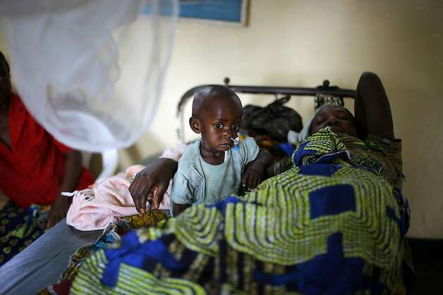 Thomas Medishimiye, 2, sufering from malaria, sits on his bed next to his mother at Rutshuru hospital, now under control of M23 rebels some 75kms (48 miles) north of Goma, eastern Congo, Saturday, Aug. 4, 2012. Doctors Without Borders reported Congo's army now controls only the city of Goma and the village of Kibumba, 10 kilometers (six miles) outside Goma. Now the rebels hold all towns going north as far as Rutshuru and are threatening to besiege Goma. The U.N. Security Council on Thursday demanded that the M23 rebel group halt any advances toward Goma. Photo: Jerome Delay, Associated Press / SF