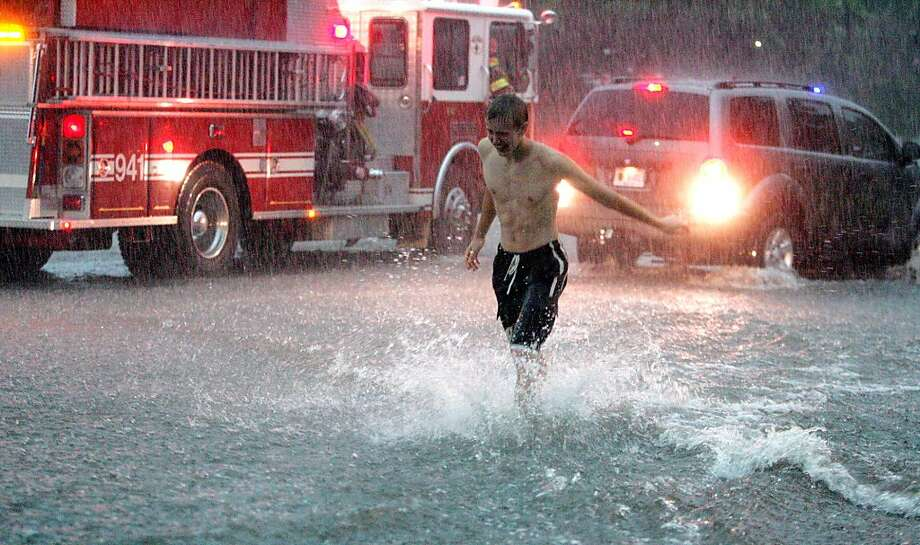 A passenger struggles to walk back to his vehicle stopped on a flooded US 20 after a severe thunderstorm went through the area with high winds and torrential downpour Saturday August 4, 2012 in New Carlisle, Ind. Photo: Bob Wellinski, Associated Press