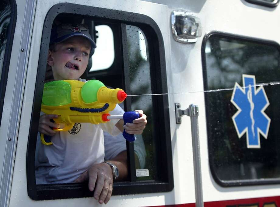 Don't thank me, just doing my job:Seven-year-old honorary EMT  Carson Vink, riding in an ambulance in the Grand Haven (Mich.) Coast  Guard Festival Grand Parade, helps protect spectators from heat stroke. Photo: Ken Stevens, Associated Press