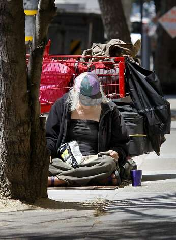 Anya, a homeless 62 year old woman, reads a book on Page Street.  She is awaiting her first Social Security payment in a few months. San Francisco's controversial sit lie law, which makes it against the law to sit or lie on a city sidewalk, is being enforced exclusively in the Haight Ashbury neighborhood. Photo: Brant Ward, The Chronicle