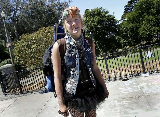 Raven Hadar, who is visiting San Francisco, pauses just inside Golden Gate Park, where she and her cat are warming in the morning sun. San Francisco's controversial sit lie law, which makes it against the law to sit or lie on a city sidewalk, is being enforced exclusively in the Haight Ashbury neighborhood. Photo: Brant Ward, The Chronicle
