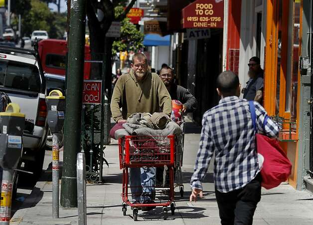 Justin O'Brien walks east on Haight Street with his familiar red shopping cart.  He has amassed over 30 sit/lie citations in the last year. In the first year of enforcement, the San Francisco Police department handed out dozens of sit/lie citations, mostly to longtime homeless people who have problems with alcohol. Photo: Brant Ward, The Chronicle