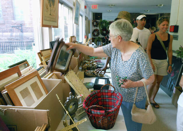 "Visitors to Operation Hope's tag sale Saturday browse picture frames in the ""art department"" at First Church Congregational, the host site. Photo: Mike Lauterborn / Fairfield Citizen contributed"