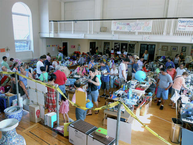People browse books and small appliances in the meeting hall at First Church Congregational, which hosted the Operation Hope tag sale on Saturday and Sunday. Photo: Mike Lauterborn / Fairfield Citizen contributed