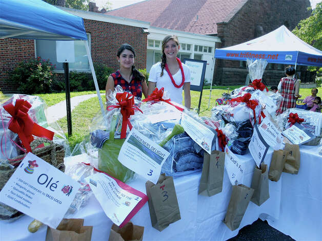 Daniella Garzon and Victoria Godfred, Operation Hope tag sale volunteers, at the event's raffle table Saturday. Photo: Mike Lauterborn / Fairfield Citizen contributed