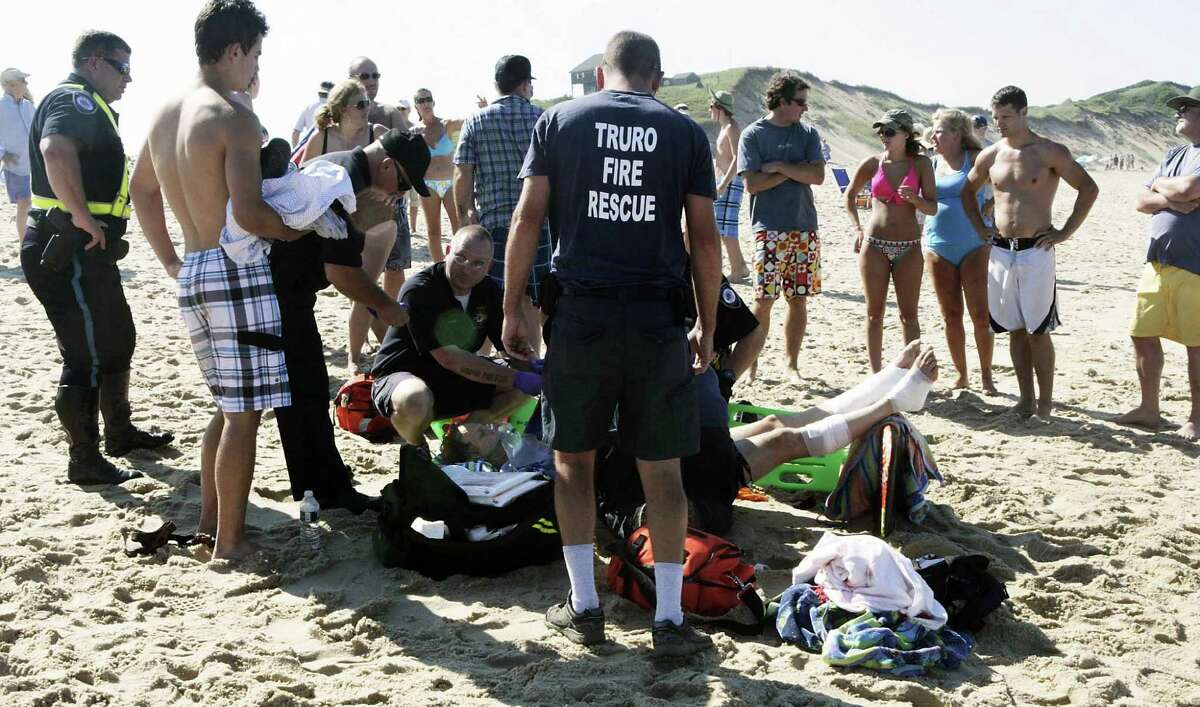 TRURO, MA - JULY 30: A man is treated for a shark bite on his legs at Cape Cod's Ballston Beach July 30, 2012 in Truro, Massachusetts. There have been numerous shark sightings off the Cape Cod coast this summer.