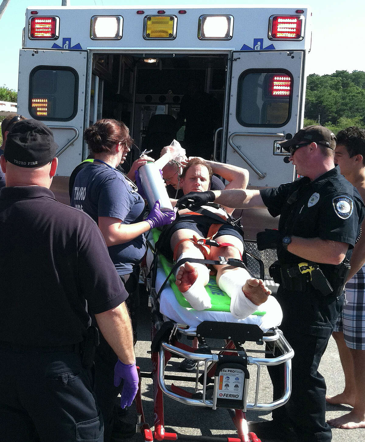 In this Monday, July 30, 2012 photo, Christopher Myers is loaded on an ambulance at Ballston Beach in Truro, Mass., after sustaining bite wounds to his legs while swimming. The beach, on Cape Cod, remained open Tuesday as authorities tried to determine whether it was a shark that attacked him. (AP Photo/Cape Cod Times, Eric Williams) INTERNET OUT. MAGS OUT. TV OUT. NO ARCHIVING WITHOUT PERMISSION. NO SALES. MANDATORY CREDIT: ERIC WILLIAMS/CAPE COD TIMES.