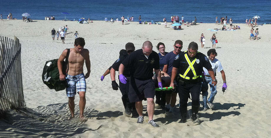 In this Monday, July 30, 2012 photo, Christopher Myers is carried off Ballston Beach in Truro, Mass., after sustaining bite wounds to his legs while swimming. The beach, on Cape Cod, remained open Tuesday as authorities tried to determine whether it was a shark that attacked him.  (AP Photo/Cape Cod Times,  Eric Williams)   INTERNET OUT. MAGS OUT. TV OUT. NO ARCHIVING WITHOUT PERMISSION. NO SALES. MANDATORY CREDIT: ERIC WILLIAMS/CAPE COD TIMES. Photo: Eric Williams, AP / Cape Cod Times