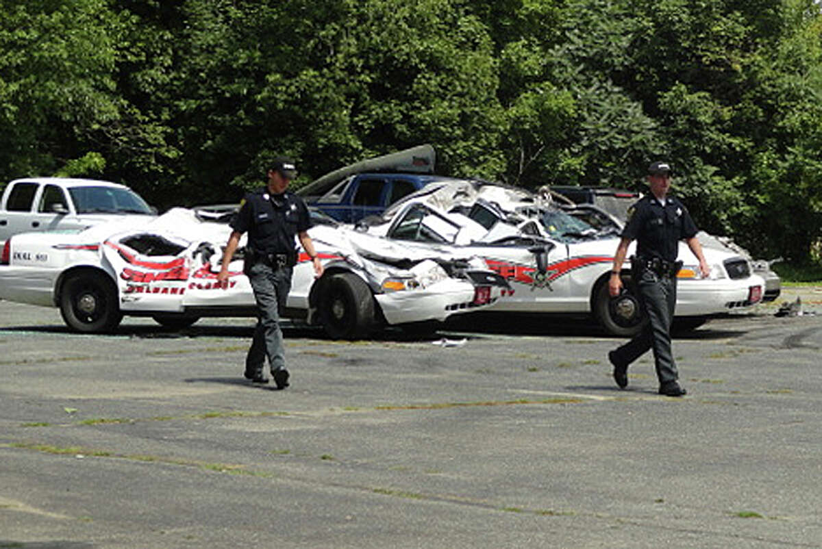 Sheriff officers walk past crushed cruisers at the Orleans County Sheriff's Department in Newport, Vt., Thursday, Aug. 2, 2012. Authorities say 34-year old Vermont farmer Roger Pion, angry over a recent arrest last month on charges of resisting arrest and marijuana possession, used a large tractor like a monster truck, destroying seven police cruisers.