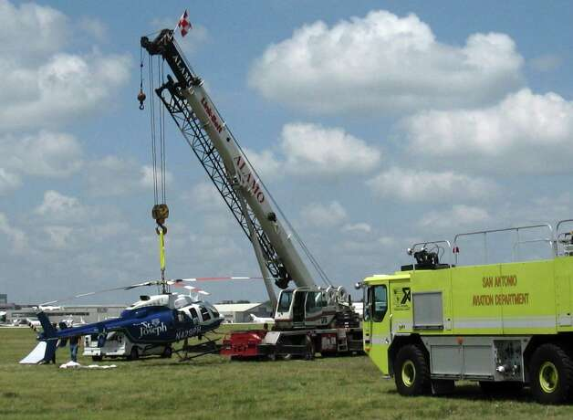 "A crane begins to remove the medical helicopter after it landed safely on mattresses at San   Antonio International  Airport. All four people aboard the helicopter were uninjured. ""We were glad it worked out,"" San Antonio Fire Department Capt. Kevin Campbell said. ""But no, I don't think I want to do that ever again."" Photo: Aircraft Rescue Fire Fighters / Aircraft Rescue Fire Fighters"