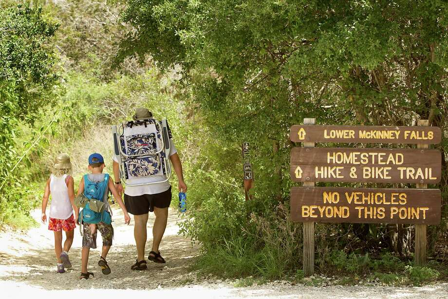 Nicholas Dana (right) takes his girlfriend's children, Shaylyn Shaeffer (left) and G.T. Paice, to McKinney Falls State Park, where corporate advertising might increase the signage. Photo: Laura Skelding, Austin American-Statesman