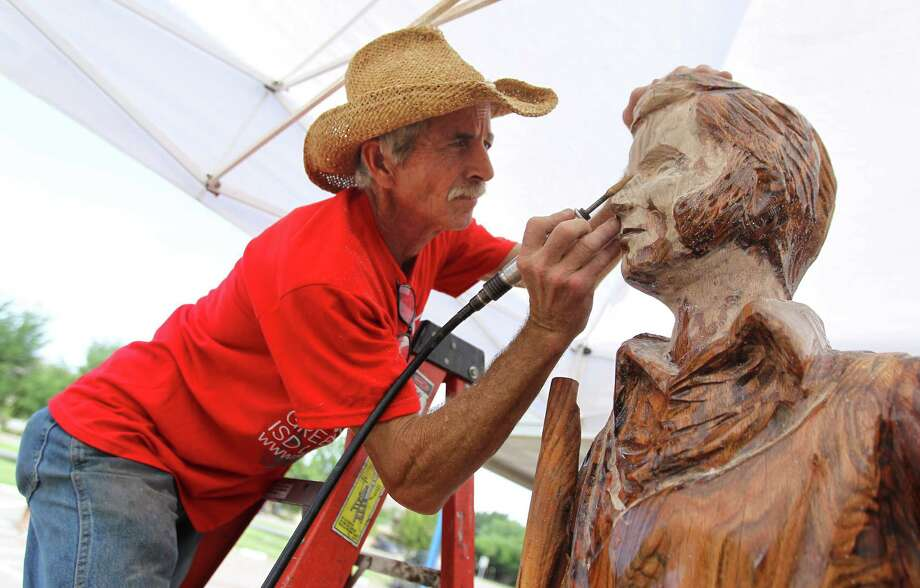 Artist Jim Phillips carves a sculpture of the legendary James Bowie into a dead tree that was planted in front of Bowie Elementary School in Greenville in 1963 and died in 2011. Photo: Mona Reeder, Dallas Morning News / The Dallas Morning News