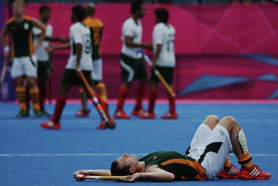 Andrew Cronje of South Africa lays on the pitch after losing 5-4 to Pakistan during the Men's Hockey match between Pakistan and South Africa at Riverbank Arena Hockey Centre in London. Photo: Daniel Berehulak, Getty Images / 2012 Getty Images