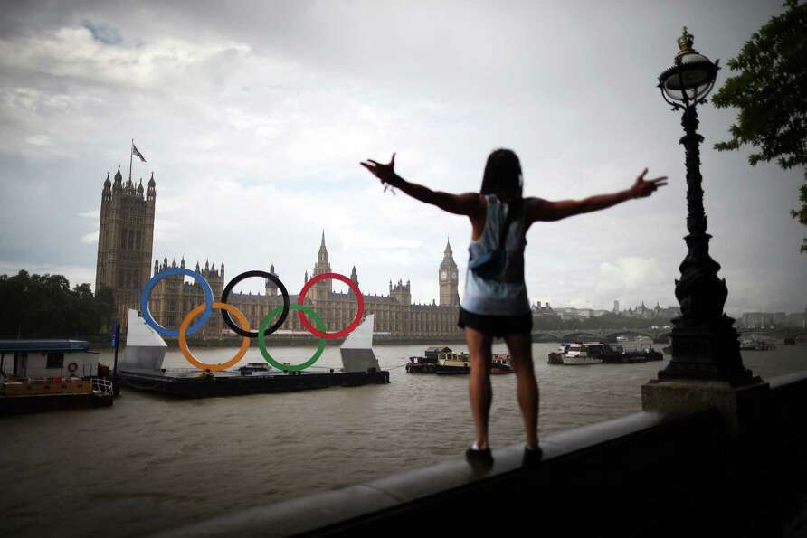 A tourist gestures in a rain shower as he looks at giant Olympic rings in the River Thames opposite