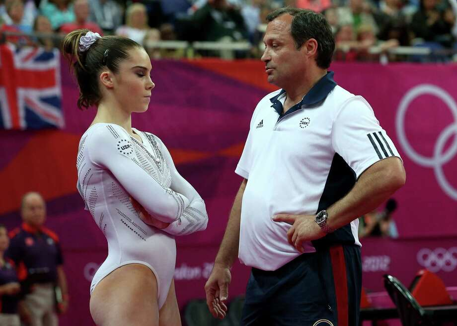 (L-R) McKayla Maroney of the United States looks on as she is consoled by coach Yin Alvarez after she fell on a dismount while competing in the Artistic Gymnastics Women's Vault Final. Photo: Ronald Martinez, Getty Images / 2012 Getty Images