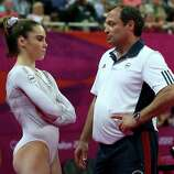 (L-R) McKayla Maroney of the United States looks on as she is consoled by coach Yin Alvarez after she fell on a dismount while competing in the Artistic Gymnastics Women's Vault Final.