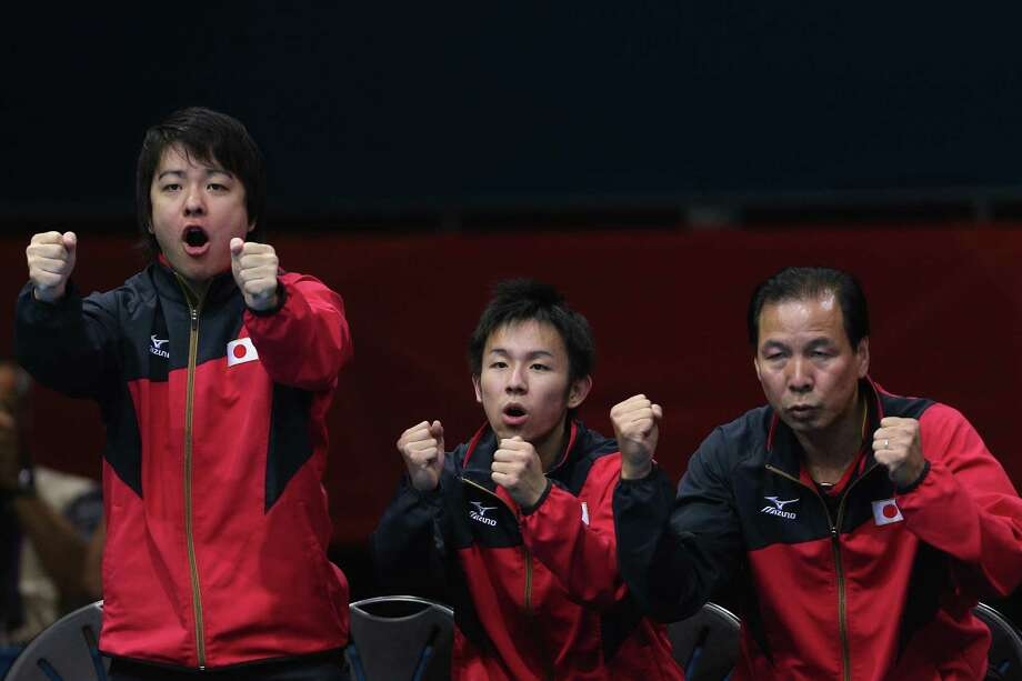 Seiya Kishikawa, Koki Niwa and their coach of Japan celebrate during Men's Team Table Tennis quarterfinal match against team of Hong Kong, China. Photo: Feng Li, Getty Images / 2012 Getty Images