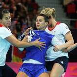 Vesna Milanovic-Litre (center) #20 of Croatia is tied up by Yvonne Leuthold (L) #13 and Nina Heglund (R) #5 of Great Britain during the Women's Handball Preliminaries Group A match between Great Britain and Croatia at the Copper Box in London.