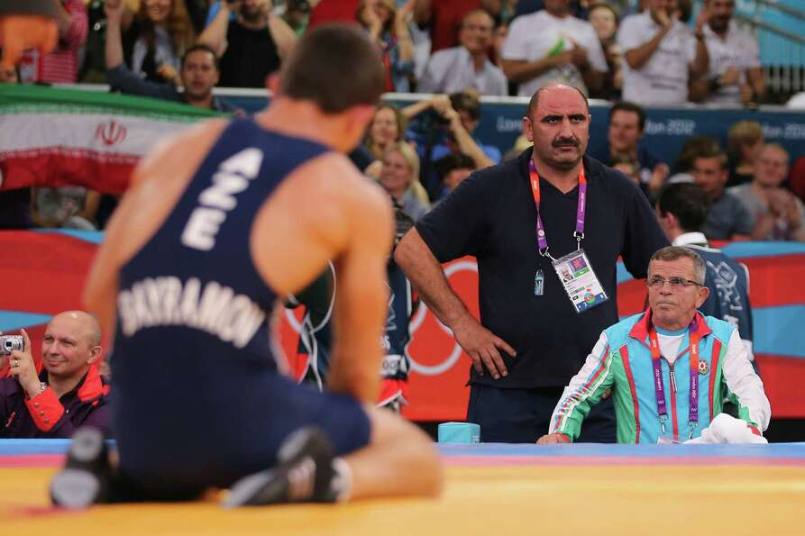 Rovshan Bayramov of Azerbaijan and his Coaches look dejected after losing against Hamid Mohammad Sor