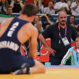 Rovshan Bayramov of Azerbaijan and his Coaches look dejected after losing against Hamid Mohammad Soryan Reihanpour of Islamic Republic of Iran during the Men's Greco-Roman 55 kg Wrestling Gold Medal bout at ExCeL in London.