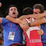 Hamid Mohammad Soryan Reihanpour of Islamic Republic of Iran celebrates winning his Men's Greco-Roman 55 kg Wrestling Gold Medal bout against Rovshan Bayramov of Azerbaijan with his Coaches.