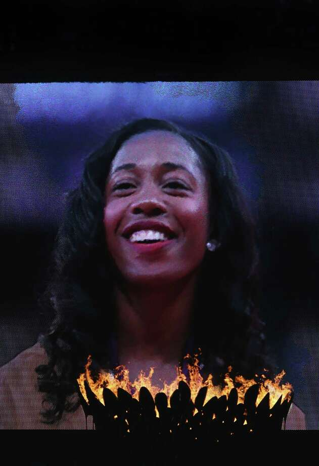 A view of the Olympic torch and video screen as Gold medalist Shelly-Ann Fraser-Pryce of Jamaica poses on the podium for Women's 100m. Photo: Ronald Martinez, Getty Images / 2012 Getty Images