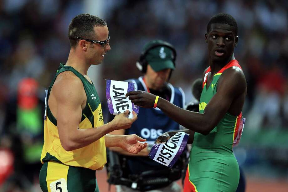 Oscar Pistorius (L) of South Africa exchanges bibs with Kirani James (R) of Grenada after the Men's 400m semifinal. Photo: Phil Walter, Getty Images / 2012 Getty Images