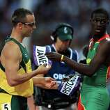 Oscar Pistorius (L) of South Africa exchanges bibs with Kirani James (R) of Grenada after the Men's 400m semifinal.