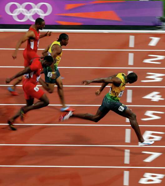 Usain Bolt of Jamaica  crosses he line to win gold in the Men's 100m Final at the Olympic Stadium in