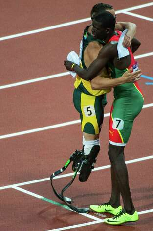 South Africa's Oscar Pistorius, left, hugs Kirani James of Grenada after their heat in the men's 400-meter semifinals at the 2012 London Olympics on Sunday, Aug. 5, 2012. James was the top qualifier from the heat. Pistorius failed to advance. Photo: Smiley N. Pool, Houston Chronicle / © 2012  Houston Chronicle
