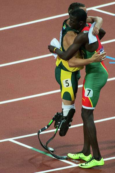South Africa's Oscar Pistorius, left, hugs Kirani James of Grenada after their heat in the men's 400