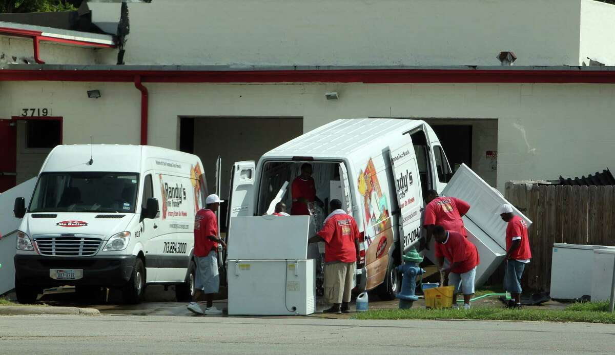 Employees wash Randy's Fine Foods Grocery Store on Wheels vans. The company accepts food stamps and cash for the mobile grocery service, and most of its customers have an appetite for junk food.