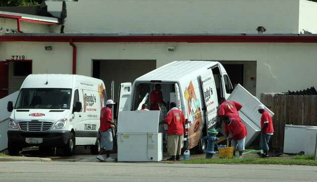 Employees wash Randy's Fine Foods Grocery Store on Wheels vans. The company accepts food stamps and cash for the mobile grocery service, and most of its customers have an appetite for junk food. Photo: James Nielsen / © Houston Chronicle 2012